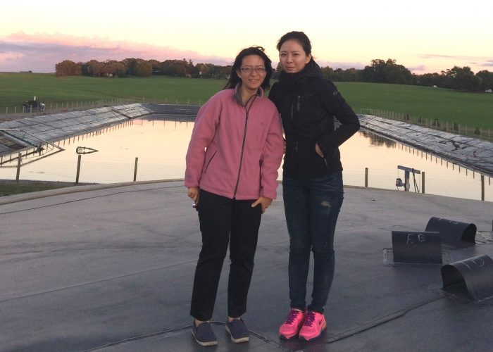 Young representatives from Taiwan government during a tour of an RCM digester in Pennsylvania. They are standing on the membrane cover which swells during maximum manure input. Manure storage lagoon is in background. Due to odor reduction suburban homes continue to be built close to this farm.